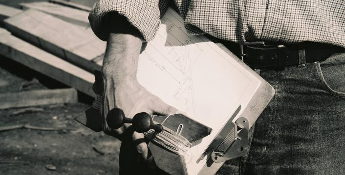 A black and white photo of a man holding a clipboard.